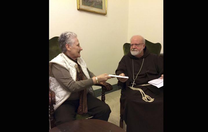 Marie Collins und Kardinal Sean O'Malley bei der Übergabe eines Briefes
