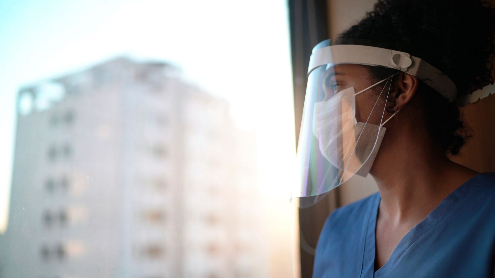 Nurse with protective face mask looking through window at hospital