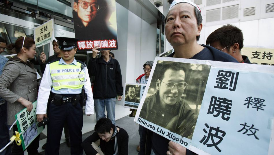 A pro-democracy protester in Hong Kong holds a placard with a picture of Liu Xiaobo. China's most prominent dissident was sentenced to 11 years in prison on Friday.