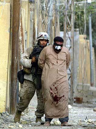 US-Soldat mit irakischem Gefangenen: Lediglich noch einige Widerstandsnester