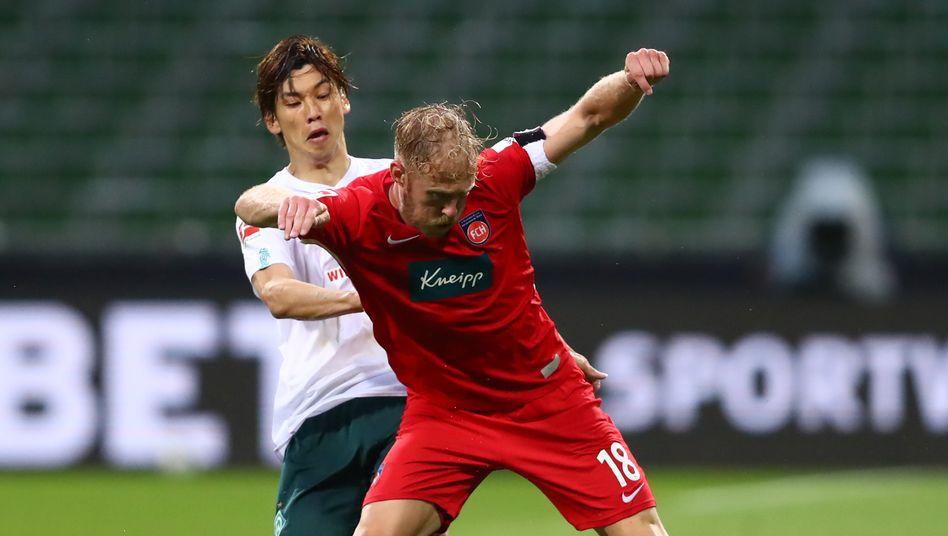 Bremens Yuya Osako gegen Heidenheims Sebastian Griesbeck im Zweikampf