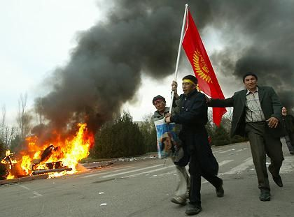 Kyrgyz opposition protesters walk with flag past a burning car outside the government building in central Bishkek.