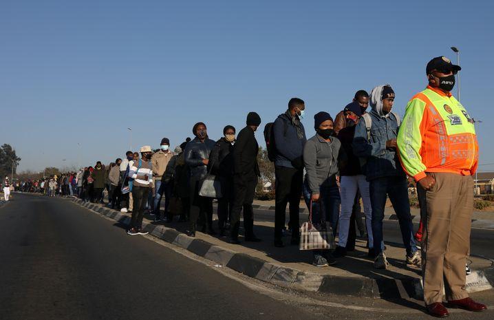 Menschen warten in Soweto, einem Vorort von Johannesburg, auf die Abholung durch ein Sammeltaxi