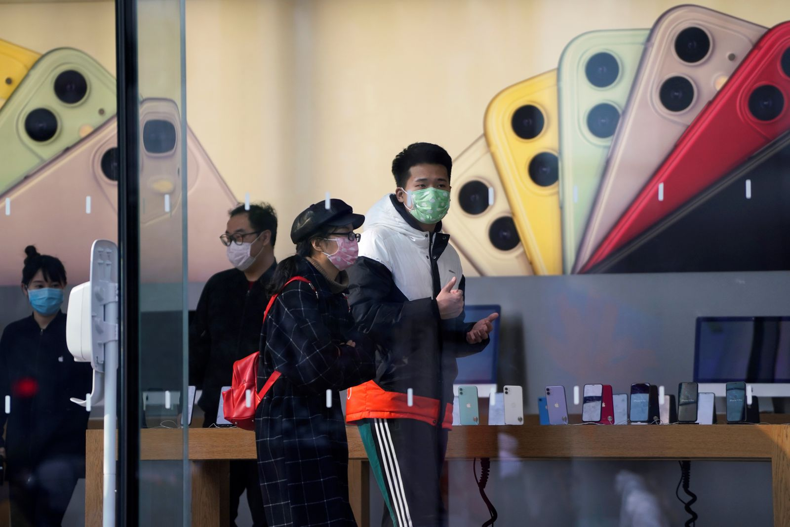 People wearing protective masks are seen in an Apple Store, as China is hit by an outbreak of the new coronavirus, in Shanghai