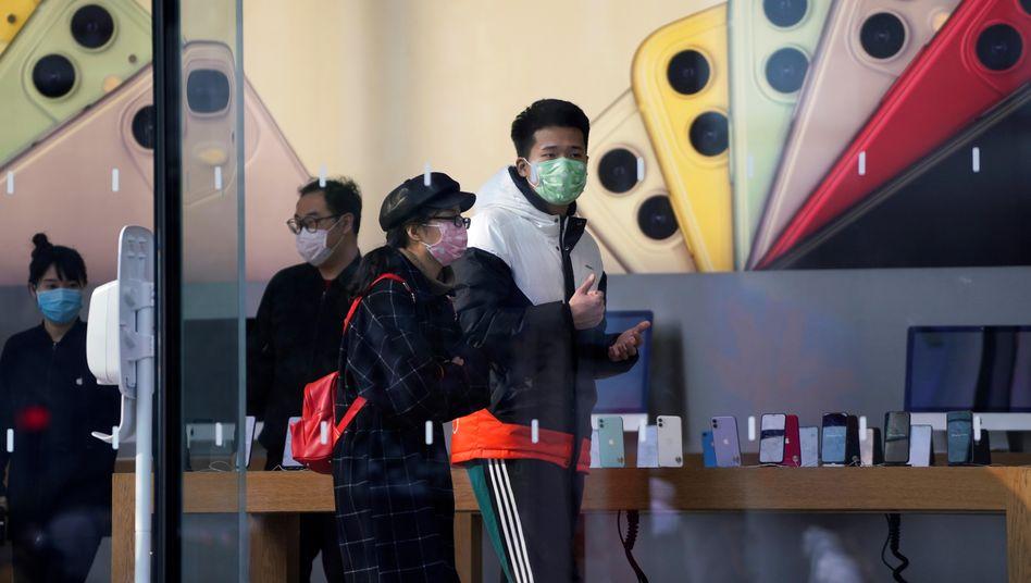 Menschen mit Schutzmasken in einer Apple-Filiale in Shanghai
