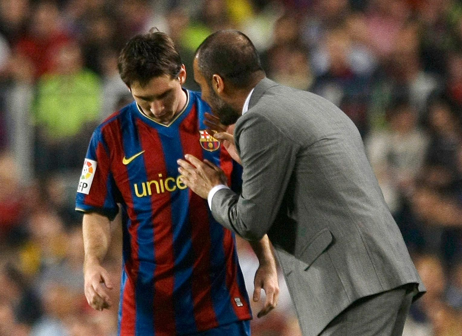 Barcelona's coach Pep Guardiola speaks to Lionel Messi during their Spanish first division soccer match against Zaragoza at Nou Camp stadium in Barcelona