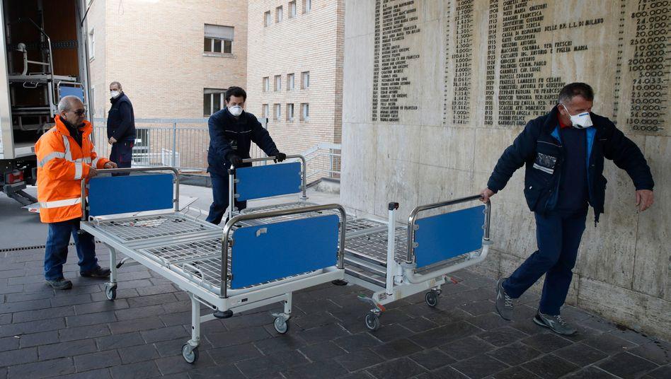 Im norditalienischen Codogno bringen Krankenhausmitarbeiter neue Betten
