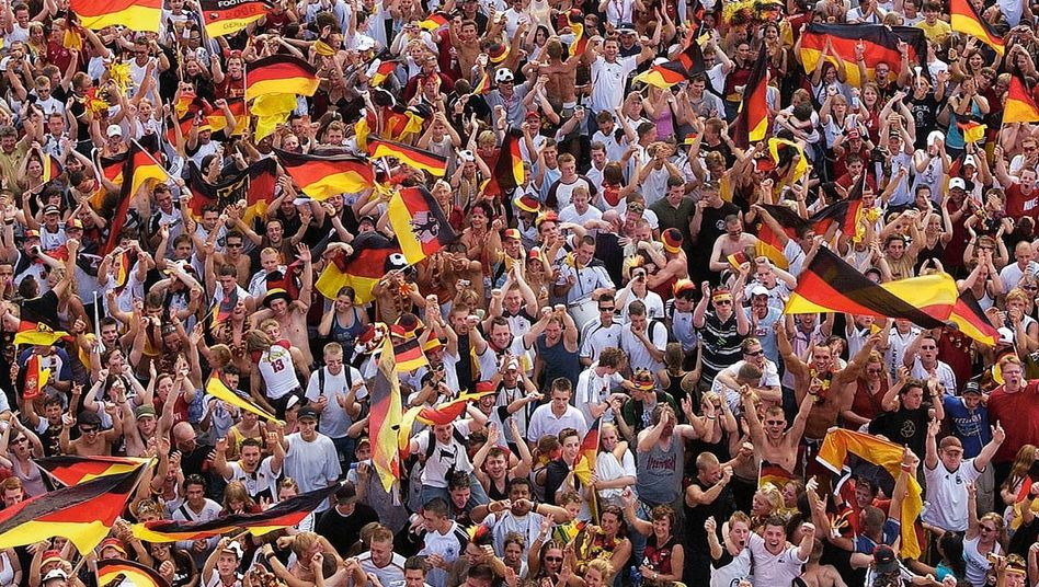 Fans in Berlin während der Fußball-WM 2006:Schwarze Wolke vor rot-goldener Sonne