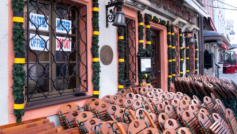 Tische und Stühle stehen vor einem geschlossenen Restaurant in der Münchner Innenstadt. Im Fenster hängen Zettel mit der Aufschrift »Gastro wieder öffnen – sofort«