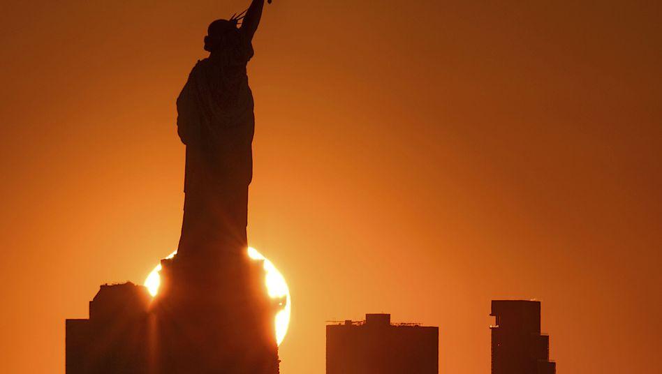 Die Sonne geht hinter der New Yorker Freiheitsstatue auf