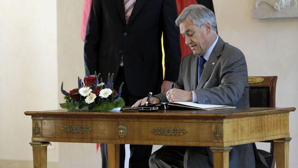 """""""Über alles, nicht wahr?"""": Der chilenische Präsident Sebastián Piñera trägt sich ins Gästebuch des Präsidialamtes ein"""