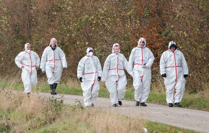 Personal in Schutzanzügen am Hof in Grumby bei Schleswig