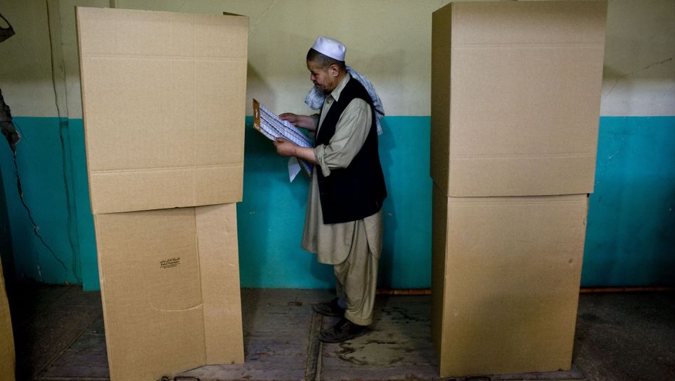 An Afghan man checks the list of candidates before casting his vote inside a polling centre in Kabul on August 20, 2009.