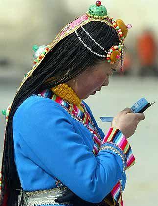 Tibeterin mit Handy: Moderne Kommunikationsmittel sind wirtschaftlich gewollt und politisch gefürchtet