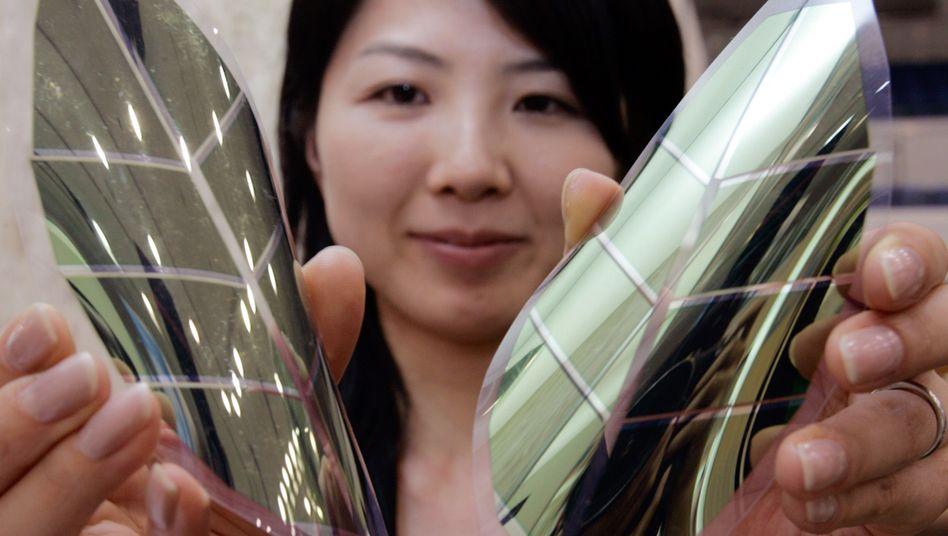 Eine Frau zeigt flexible organische Solarmodule (Symbolbild)