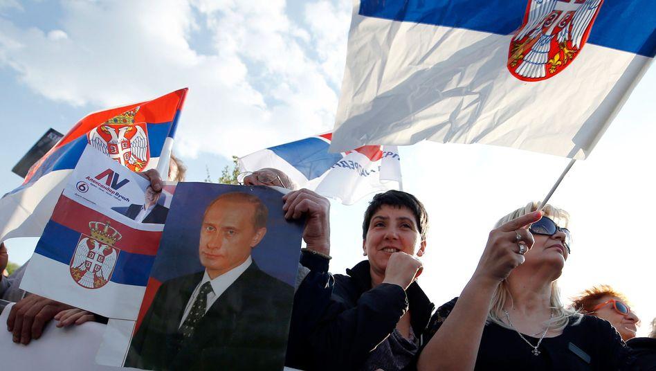 Unterstützer von Serbiens Präsidenten Vucic schwenken während der Kundgebung in Belgrad serbische Flaggen - und halten Bild des russischen Präsidenten Putin.
