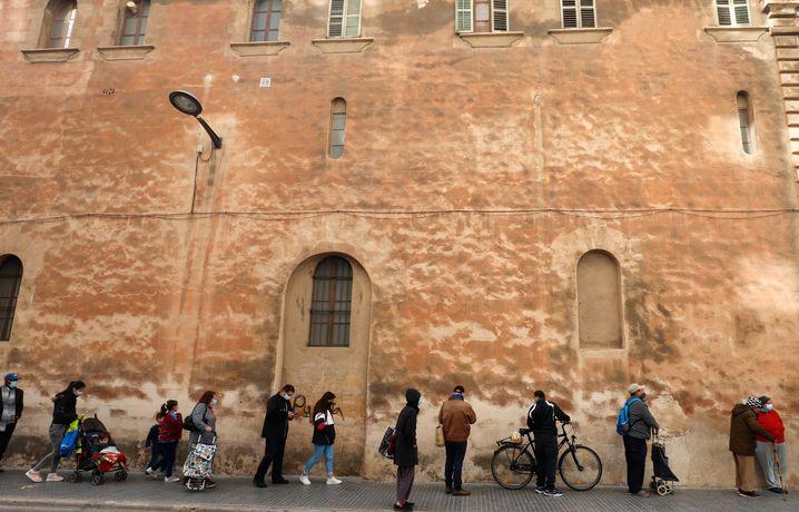 Hilfsbedürftige warten vor der Caputxins-Kirche in Palma de Mallorca auf Essen