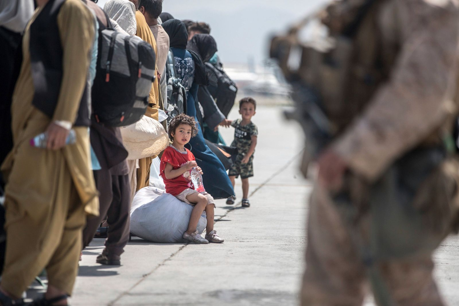 A child waits with her family to board a U.S. Air Force Boeing C-17 Globemaster III during an evacuation at Hamid Karzai