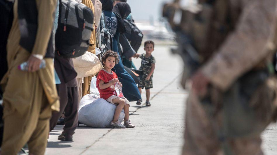 Kinder einer afghanischen Familie warten auf dem Flughafen von Kabul auf ihren Evakuierungsflug, 22. August 2021
