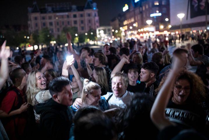Junge Menschen feiern spontan vor dem Rathaus, die Polizei schaut zu