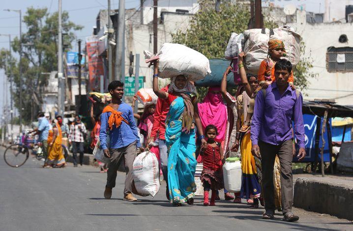 Arbeiter und ihren Familien im indischen Bhopal wollen zu Fuß in ihre Dörfer zurück