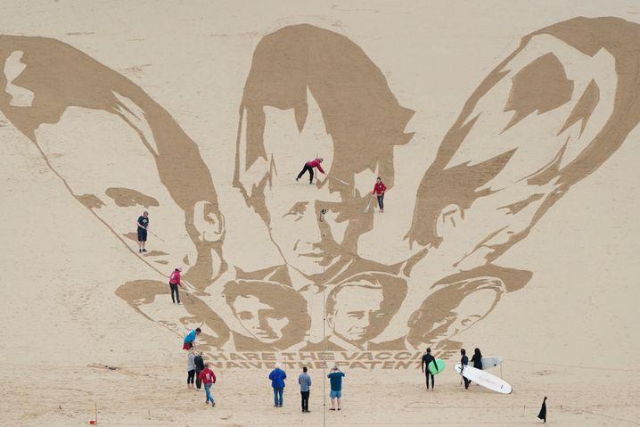 Aktivisten zeichnen die Köpfe der G7-Regierungschefs in den Sand in Cornwall, England. Sie fordern zu einer Freigabe der Impfpatente auf