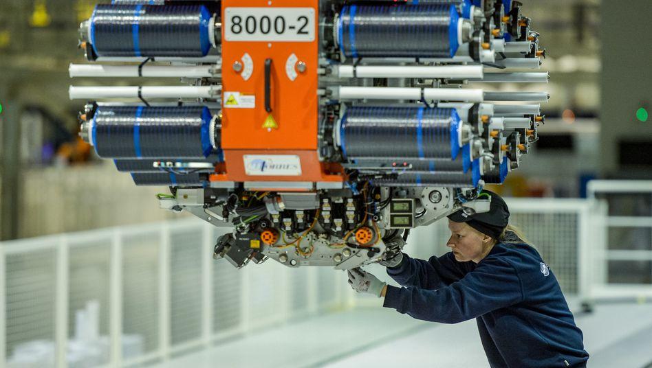 """Airbus-Mitarbeiterin arbeitet an Industrieroboter (Symbolbild): """"Sektoren mit niedriger Ansteckungsgefahr"""" zuerst geöffnet werden, etwa """"hochautomatisierte Fabriken"""""""