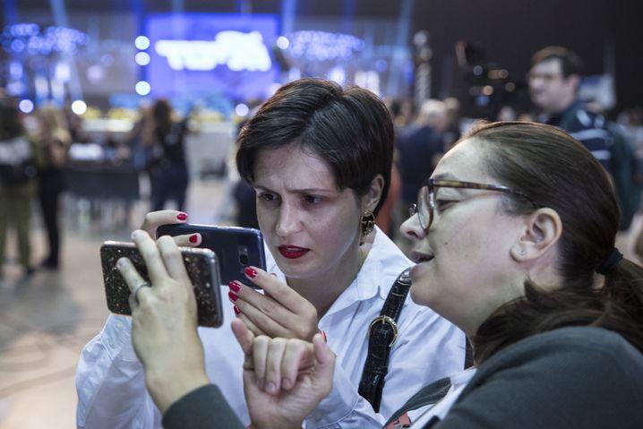 Zwei Frauen auf der Likud-Wahlparty studieren die Ergebnisse auf ihren Smartphones
