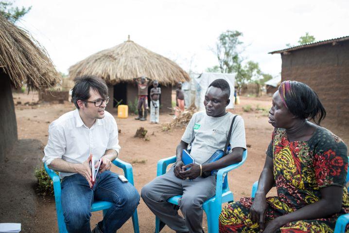 SPIEGEL-ONLINE-Redakteur Christoph Titz im Gespräch mit Selena Gaba, geflüchtet aus dem Südsudan, ( Mitte: Übersetzer) im Flüchtlingscamp Bidibidi in Uganda.