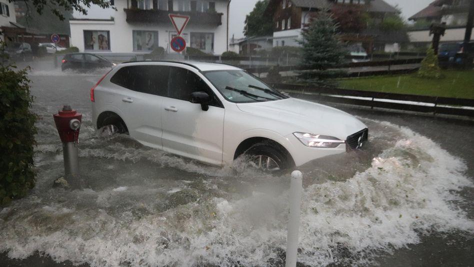Ein Auto fährt im bayerischen Blaichach durch das Wasser einer überschwemmten Straße