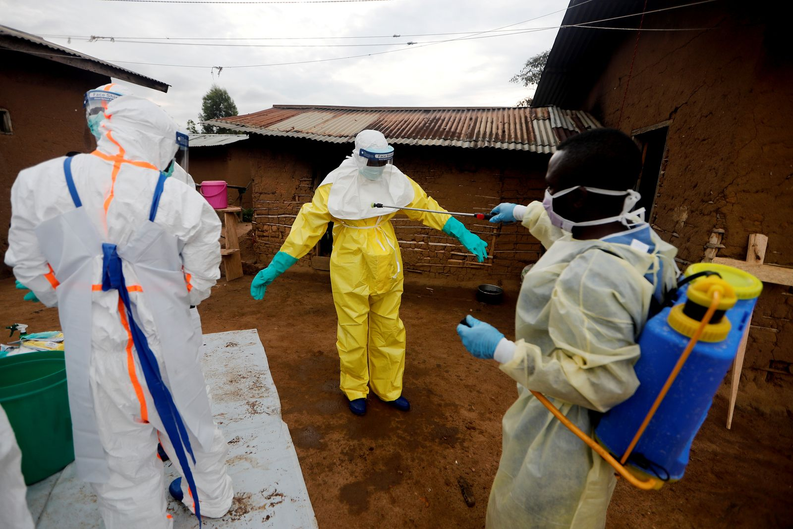 Healthcare worker Kavota Mugisha Robert decontaminates his colleague after he entered the house of 85-year-old woman suspected of dying of Ebola in the eastern Congolese town of Beni