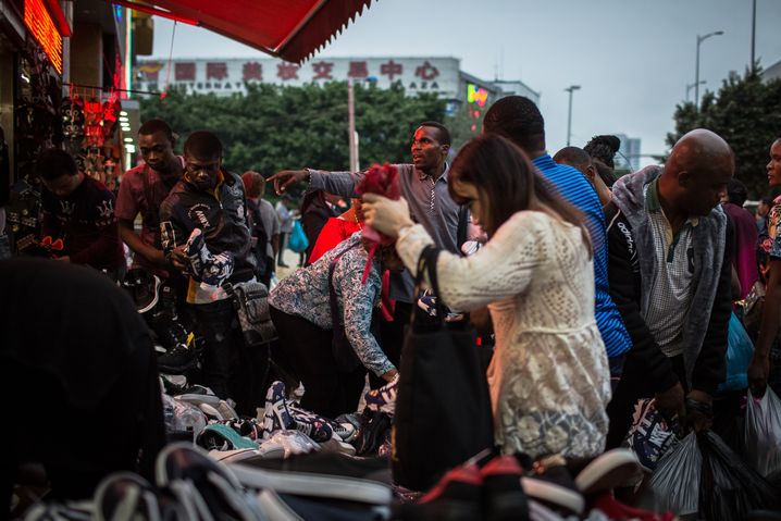 Africans and a Chinese woman look at shoes at a market in Guangzhou.