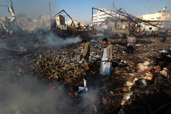 Yemeni men inspect the damage at the site of a Saudi-led coalition air strike which hit a sewing workshop in the capital Sanaa, on Feb. 14, 2016.