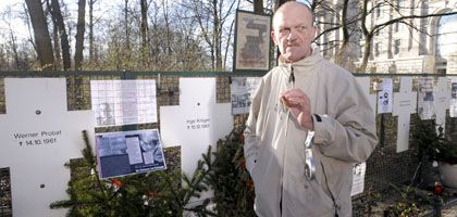 """Dauerprotestierer Gustav Rust vor den Informationstafeln, die er zwischen die Kreuze des Mahnmals für Maueropfer in der Nähe des Reichstags gehängt hat: """"Lulle, dit is Knastjargon"""""""