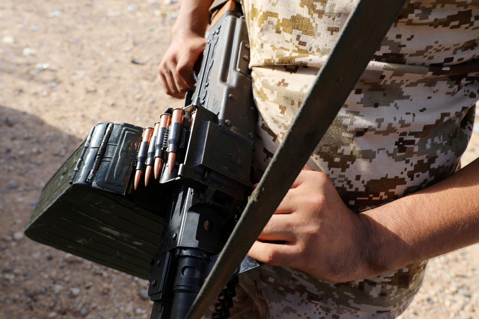 FILE PHOTO: A member of the Libyan internationally recognised government forces carries a weapon in Ain Zara