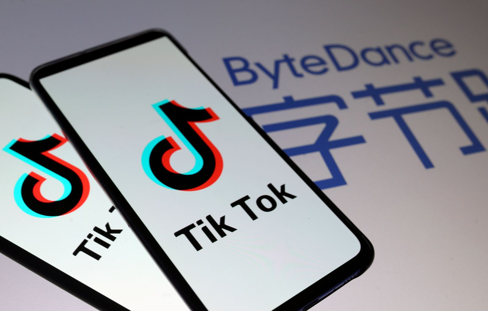 FILE PHOTO: TikTok logos are seen on smartphones in front of displayed ByteDance logo in this illustration