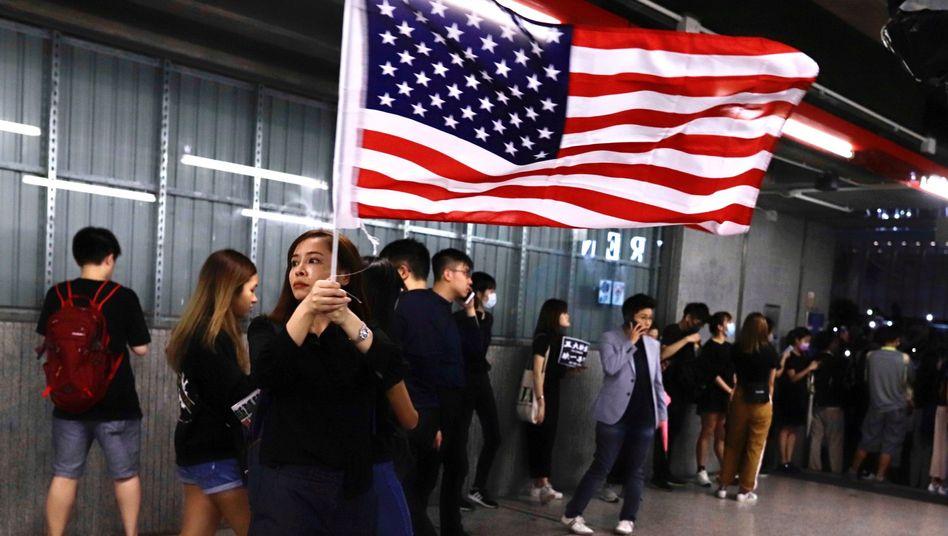 Eine Demonstrantin in Hongkong schwingt eine US-Fahne