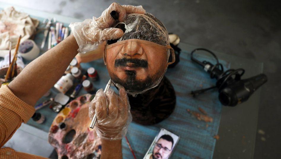 Der brasilianische Künstler Jorge Silva Roriz malt eine personalisierte Schutzmaske in seinem Haus in Rio
