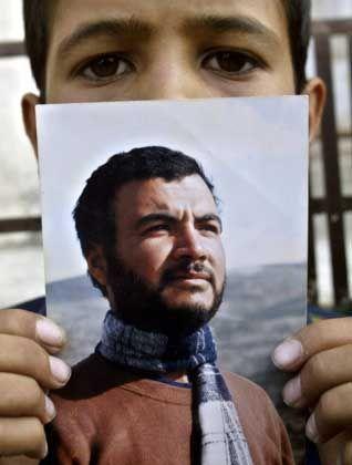 """Ein Junge mit dem Bild des getöteten Hamas-Anführers: """"Dieser Mann lebte ein gefährliches Leben"""""""