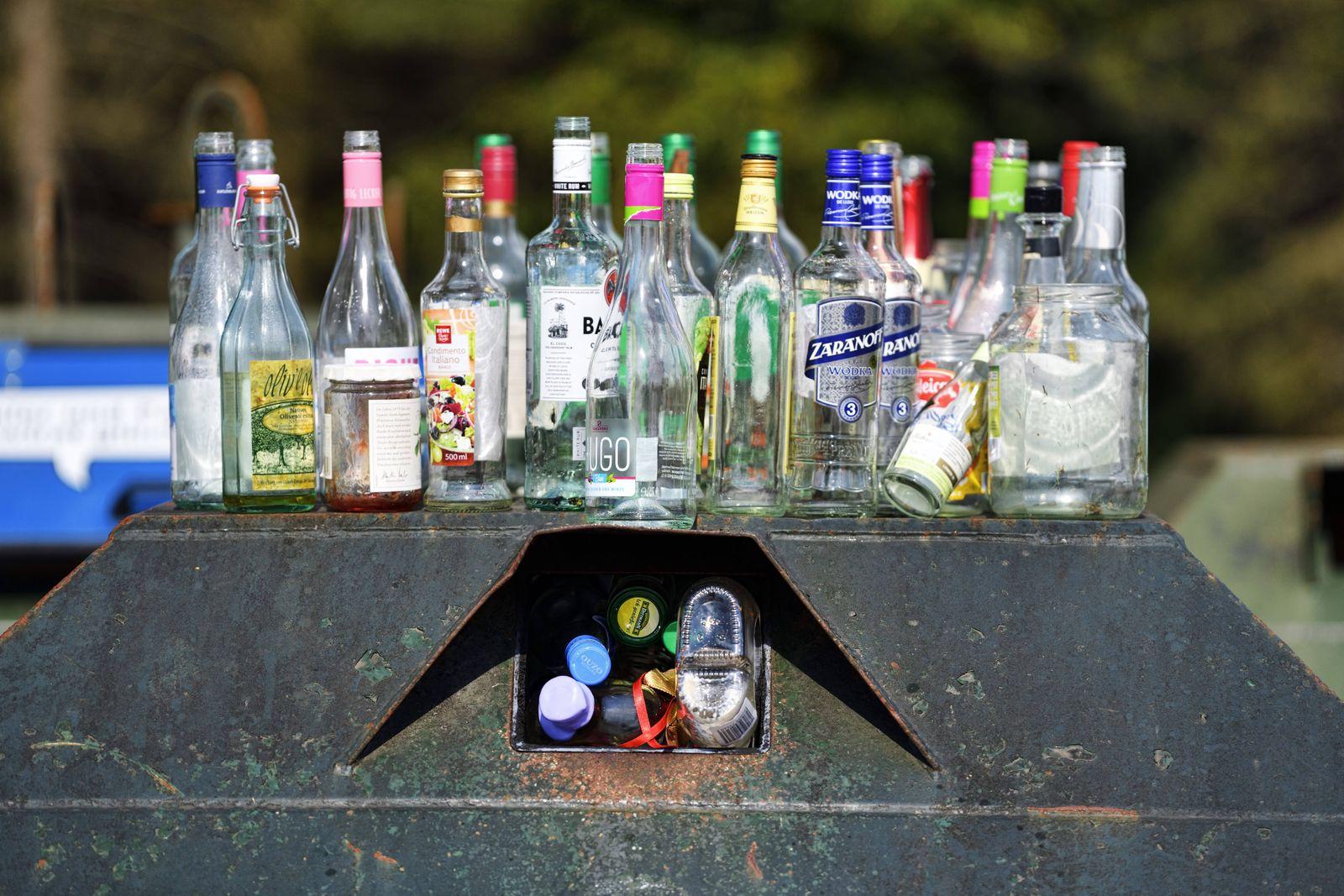 Leere Flaschen stehen auf einem Altglascontainer *** Empty bottles standing on a bottle bank