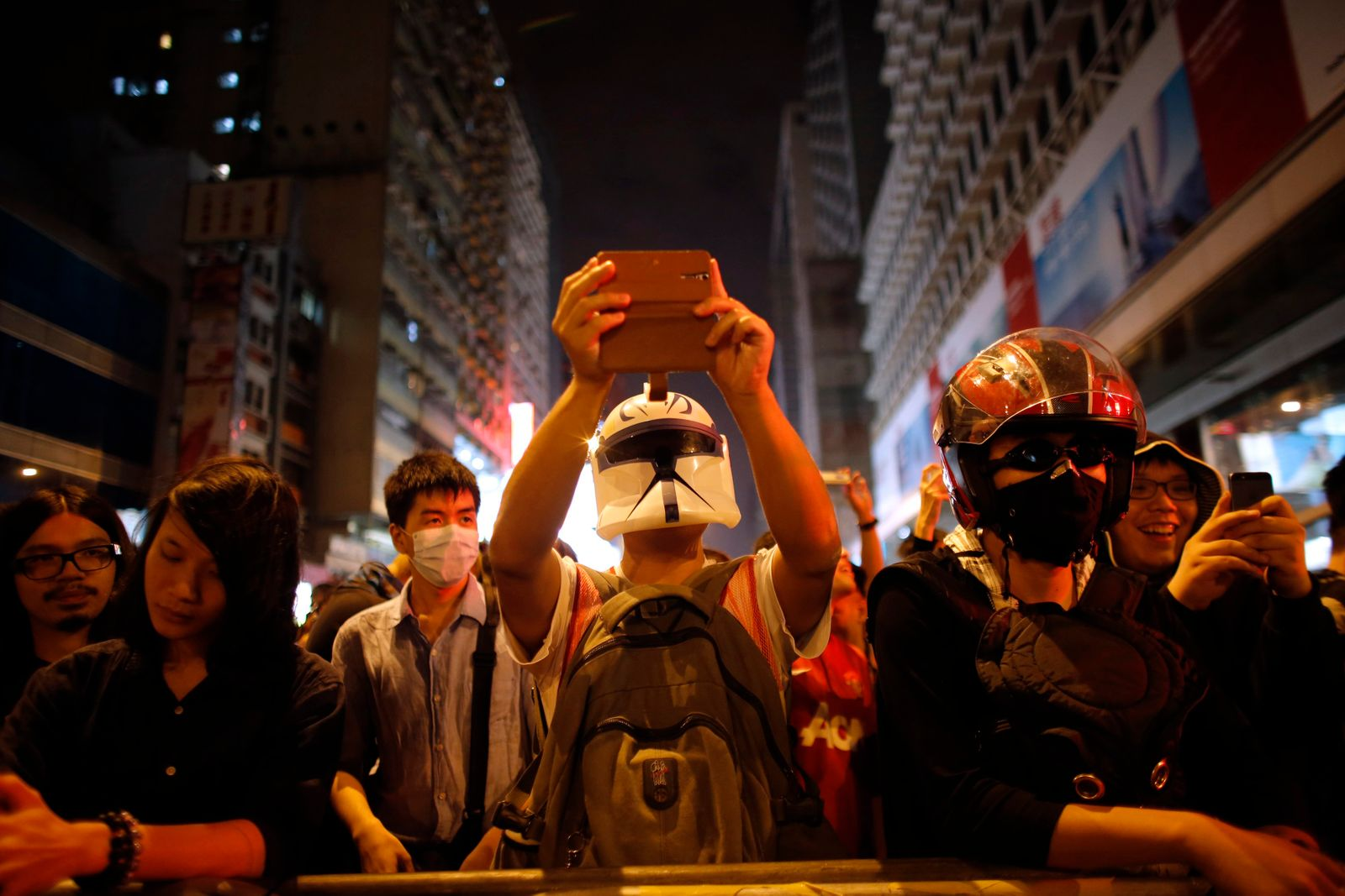 Pro-democracy protester takes a picture of riot police with his mobile phone at the Mongkok shopping district of Hong Kong
