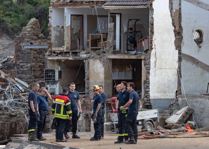 Feuerwehrleute stehen im Dorf Mayschoß vor völlig zerstörten Häusern