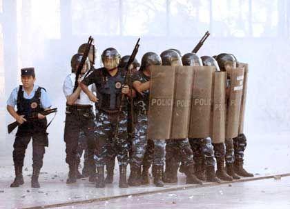 Aufmarsch in Cordoba: Sicherheitskräfte versuchten die Situation am Mittwoch wieder unter Kontrolle zu bringen, nachdem aufgebrachte Arbeiter der Stadt das Rathaus angezündet hatten. Ihre Forderungen: Zahlt uns unseren Lohn!