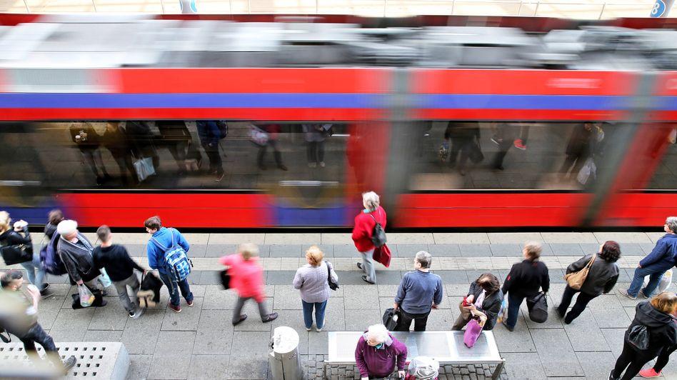 Wartende Menschen an einer Straßenbahnhaltestelle