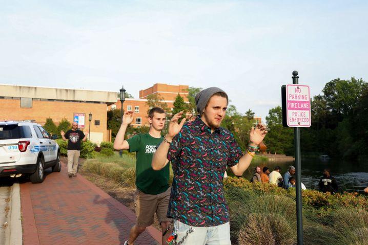 Mit erhobenen Händen verlassen Studenten den Campus