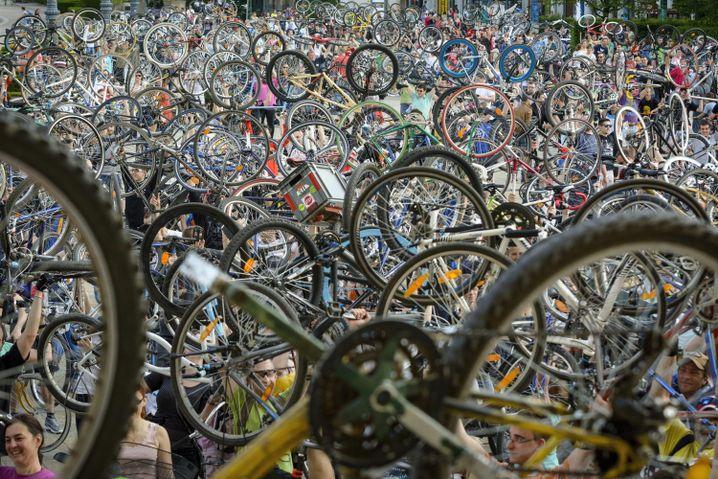 Teilnehmer der Critical Mass in Budapest, Ungarn, heben ihre Räder hoch