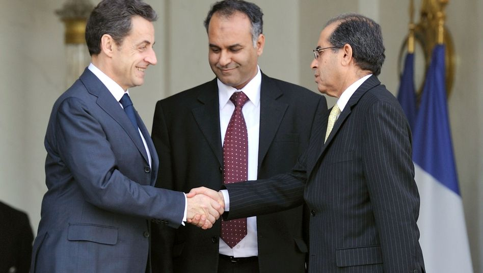 French President Nicolas Sarkozy shakes hands with members of the Libyan rebel government outside the Elysee Palace.