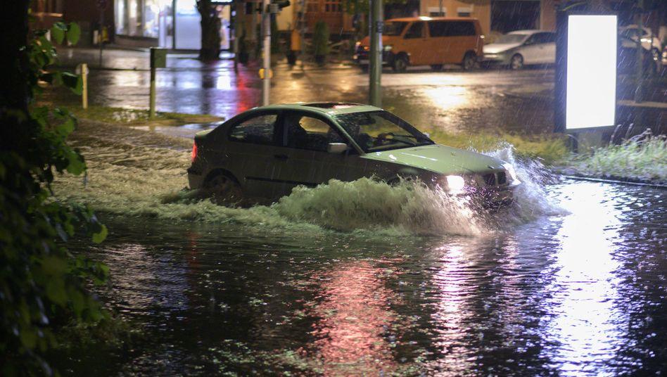Ein Pkw fährt nach einem Gewitter durch die überflutete Breite Straße in Berlin-Schmargendorf