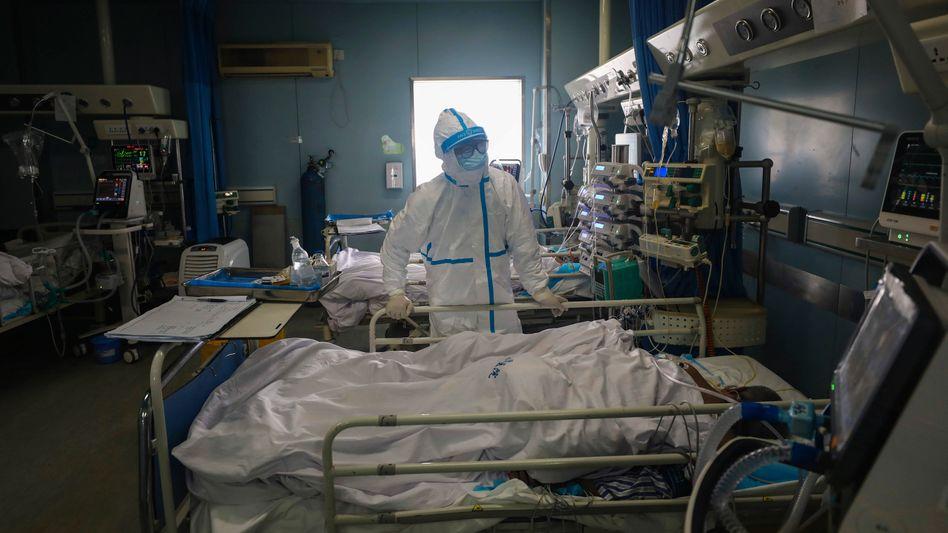 Ein Arzt bei einem Corona-Patienten in Wuhan