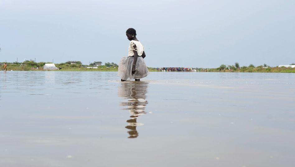 Rekordüberschwemmung im Bürgerkriegsland: Ein Mädchen watet im Südsudan durch braune Fluten